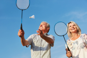 elderly couple playing badminton